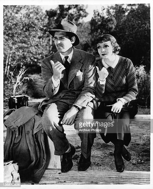Claudette Colbert and Clark Gable sitting on a wooden fence with their thumbs pointing toward the right in a scene from the film 'It Happened One...