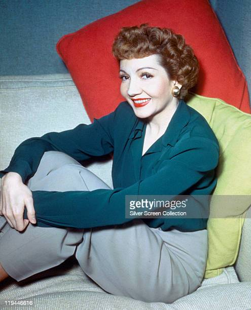 Claudette Colbert Frenchborn US actress wearing a blue blouse and grey trousers leaning against a red and a green cushion in a studio portrait circa...