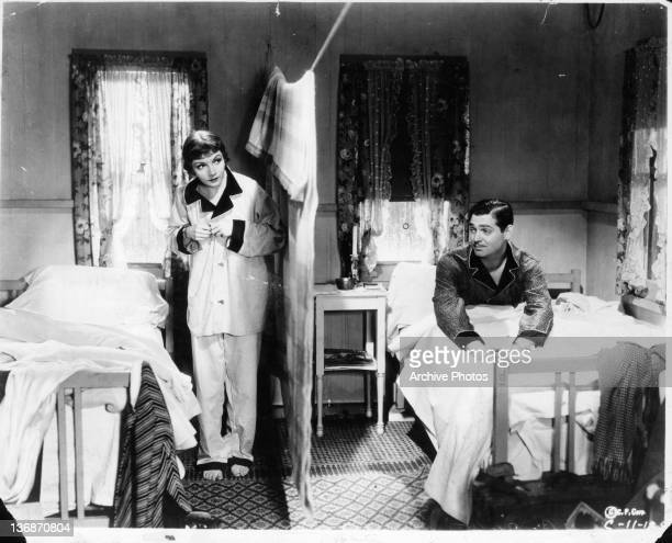 Claudette Colbert got up from her twin bed as Clark Gable sits up in his in the same room with a curtain separating them in a scene from the film 'It...