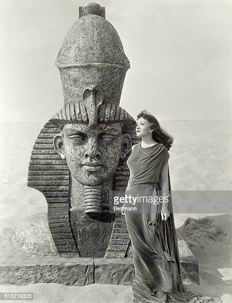 Claudette Colbert playing the title role in Cecil B DeMille's movie Cleopatra stands near an Egyptian statue