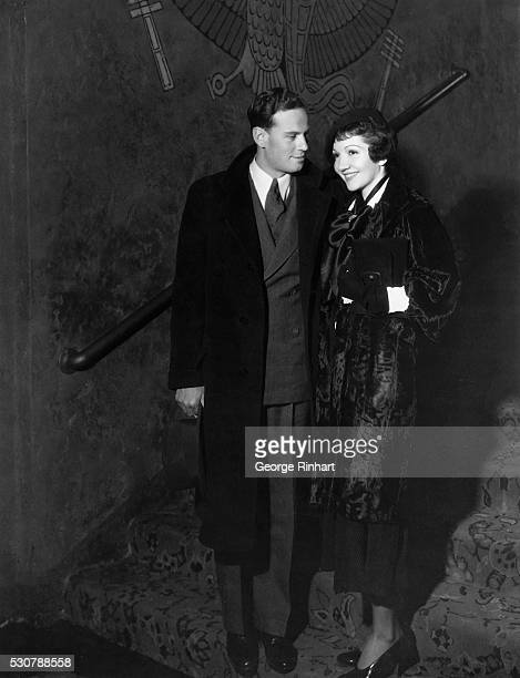 Claudette Colbert with her equally famous husband Norman Foster at the preview of Claudette's triumphant picture It Happened One Night in which she...