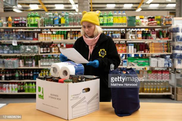 Claudia Apopii checks a food parcel list on April 3 2020 in Cardiff Wales Staff and volunteers at Cardiff Council are helping to provide emergency...