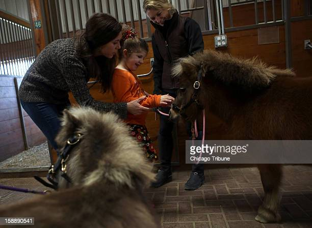 Claudia Bolle who suffers from severe autism pets miniature horses with help from her mother Charlotte Bolle left and volunteer Nancy Sobotta at...