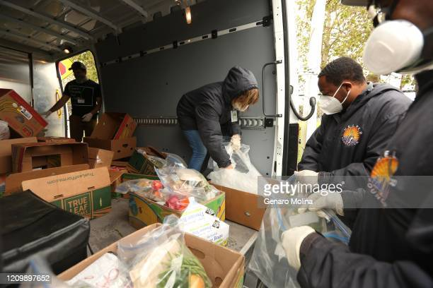 VENICE CA APRIL 09 2020 Claudia Bracho second from left Melvin Hayward III and Ebay Williams right with the HELPER Foundation prepare to deliver food...