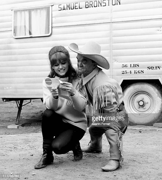 Claudia Cardinale and a dwarf during a break from filming 'Circus World' diected by Henry Hataway Madrid Spain
