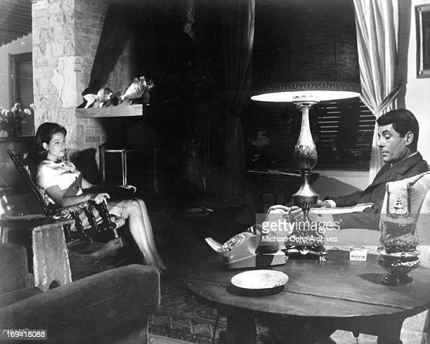 Claudia Cardinale and Philippe Nicaud sitting in chairs in a scene from the film 'The Magnificent Cuckold' 1964