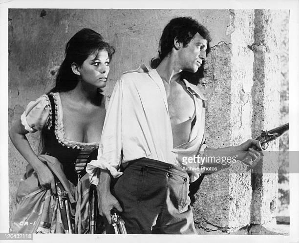 Claudia Cardinale hides behind JeanPaul Belmondo in a scene from the film 'Cartouche' 1962
