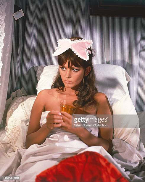 Claudia Cardinale, Italian actress, in bed holding a drink with a sleepmask on her head, circa 1960.