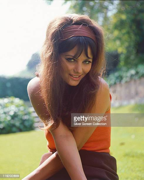 Claudia Cardinale Italian actress wearing an orange top and brown headband with her arms crossed in front of her circa 1960