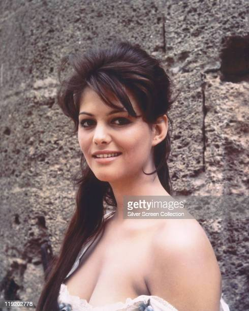 Claudia Cardinale, Italian actress, wearing low-cut top and posing before a stone wall, circa 1960.