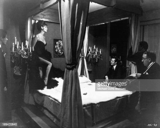 Claudia Cardinale stepping onto bed in front of men in a scene from the film 'The Magnificent Cuckold' 1964
