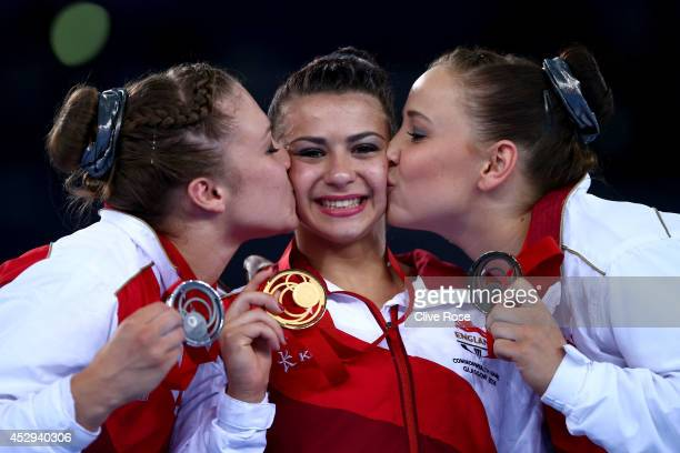 Claudia Fragapane of England is kissed on the podium by Ruby Harrold and Hannah Whelan after winning the Women's AllAround Final at the SECC Precinct...