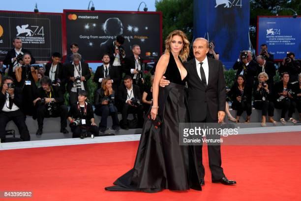 Claudia Gerini and Carlo Buccirosso walk the red carpet ahead of the 'Ammore E Malavita' screening during the 74th Venice Film Festival at Sala...