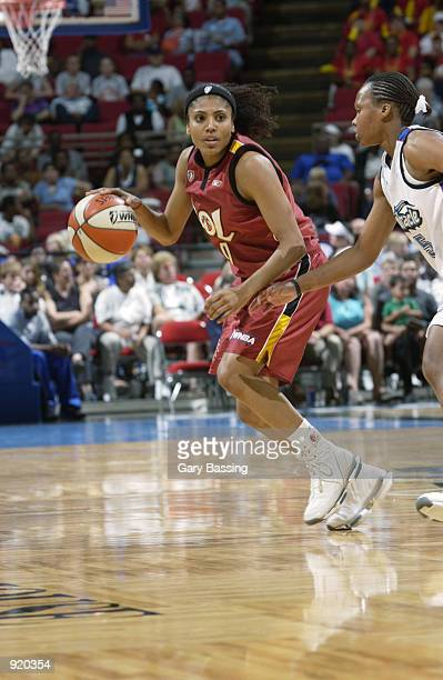 Claudia Neves of the Miami Sol drives past Elaine Powell of the Orlando Miracle in the game on June 15 2002 at TD Waterhouse Centre in Orlando...