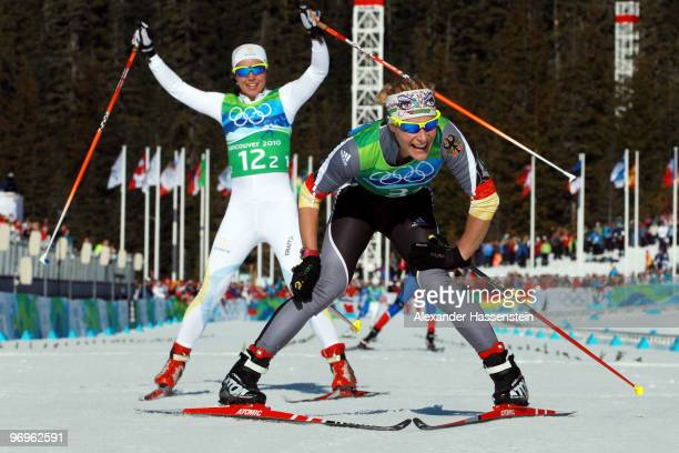 Claudia Nystad of Germany and Anna Haag of Sweden celebrate crossing the finish line during the cross country skiing ladies team sprint final on day...