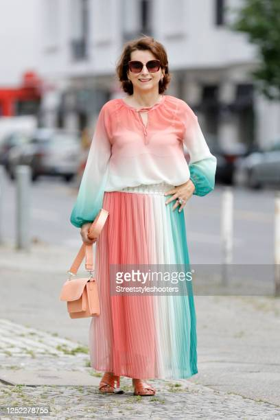 Claudia Obert, wearing a coral, creme and petrol colored long pleated skirt by Riani and a matching sheer blouse by Riani, coral slides by Claudia...