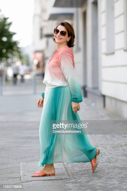Claudia Obert, wearing a coral, creme and petrol colored long pleated skirt by Riani and a matching sheer blouse by Riani and coral slides by Claudia...