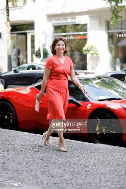Claudia Obert, wearing a red midi length dress by The Mercer N.Y., silver sandals by Claudia Obert and a gold leather mimosa clutch by Abro during a...