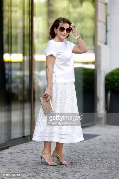 Claudia Obert, wearing a white t-shirt by Riani and a white long lace skirt by Riani, silver sandals by Claudia Obert and a gold leather mimosa...