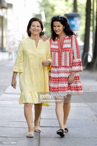 Claudia Obert, wearing a yellow tunic dress in bohemian style by Flowers for Friends and gold slides by Claudia Obert, actress Mariella Ahrens,...