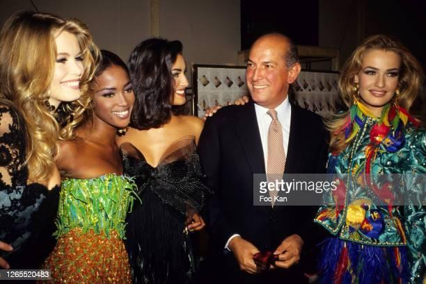 Claudia Schiffer, Naomi Campbell, a model, Oscar de La Renta and Karen Mulder attend an Oscar de La Renta show during Paris Fashion Week in the 1990s...