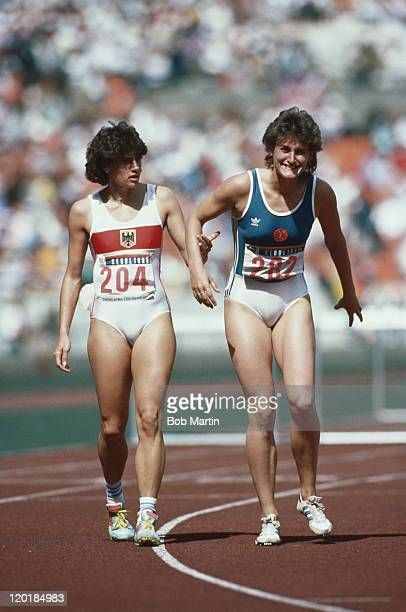 Claudia Zaczkiewicz of West Germanycomes to the aid of injured Cornelia Oschkenat of East Germany after the Women's 100 metres Hurdles at the XXIV...