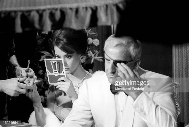 Claudine Auger fixes her makeup and Adolfo Celi his eye patch before shooting the gambling table scene at the casino of the movie Thunderball...