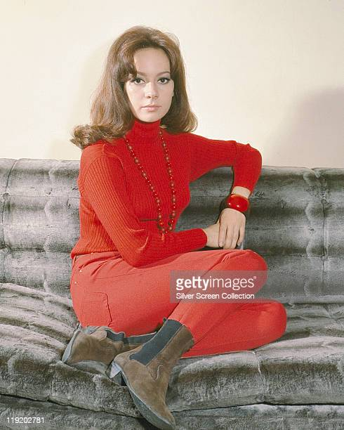 Claudine Auger French actress sitting on a grey sofa wearing a red polo neck jumper red trousers and brown suede Chelsea boots circa 1970