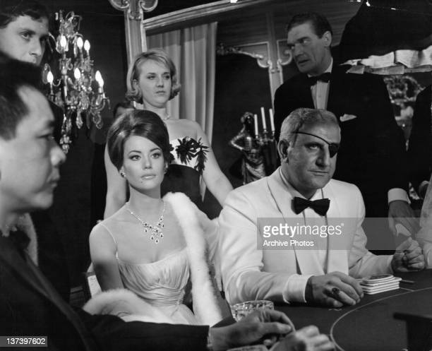 Claudine Auger wearing a white evening gown and a white fur coat sitting at a casino table next to Adolfo Celi playing the SPECTRE villain with an...