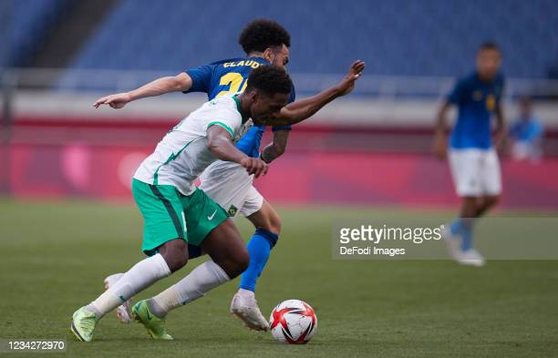 Claudinho of Brazil and Khalifah Aldawsari of Saudi Arabia battle for the ball during the Men's Group D match between Saudi Arabia and Brazil on day...