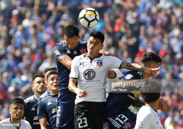 Claudio Baeza of Colo Colo goes for a header with Christian Vilches of U de Chile during a match between U de Chile and Colo Colo as part of Torneo...