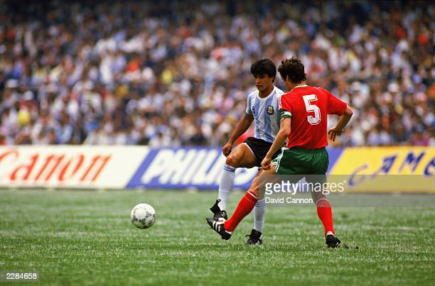 Claudio Borghi of Argentina passes the ball forward as he is closed down by Gueorgui Dimitrov of Bulgaria during the FIFA World Cup Finals 1986 Group...