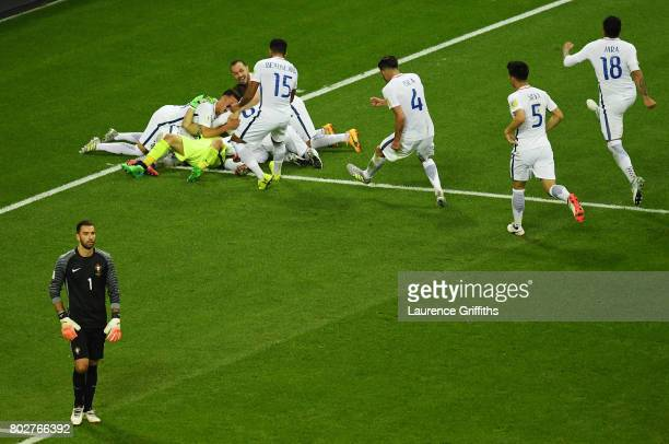 Claudio Bravo of Chile celebrates winning the penalty shoot out with his Chile team mates as Rui Patricio of Portugal looks on dejected during the...