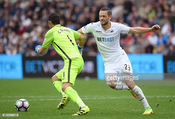 Claudio Bravo of Manchester City is put uinder pressure from Gylfi Sigurdsson of Swansea City during the Premier League match between Swansea City...