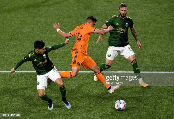 Claudio Bravo of Portland Timbers pokes the ball away from Joe Corona of Houston Dynamo as Dario Zuparic closes in during the second half of the...