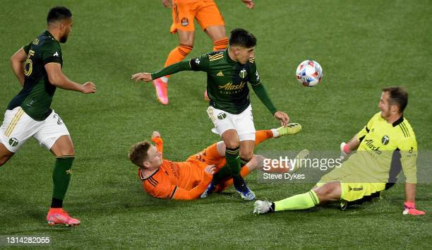 Claudio Bravo of Portland Timbers pokes the ball away from Tyler Pasher of Houston Dynamo as goalie Jeff Attinella slides in during the second half...