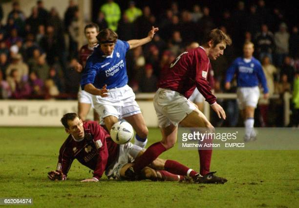 Claudio Caniggia of Rangers gets the ball past Arbroath's John McGlashan and Innes Ritchie