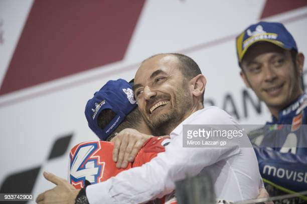 Claudio Domenicali of Italy celebrates with Andrea Dovizioso of Italy and Ducati Team on the podium at the end of the MotoGP race during the MotoGP...