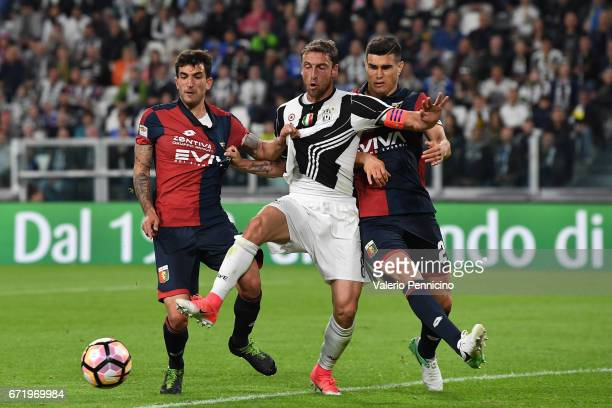 Claudio Marchisio of Juventus FC is challenged by Danilo Cataldi and Ezequiel Munoz of Genoa CFC during the Serie A match between Juventus FC and...