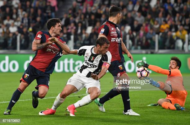 Claudio Marchisio of Juventus FC is challenged by Danilo Cataldi of Genoa CFC during the Serie A match between Juventus FC and Genoa CFC at Juventus...