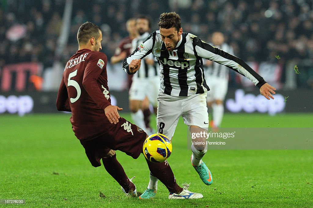 Claudio Marchisio (R) of Juventus is challenged by Valerio Di Cesare of Torino FC during the Serie A match between Juventus and Torino FC at Juventus Arena on December 1, 2012 in Turin, Italy.