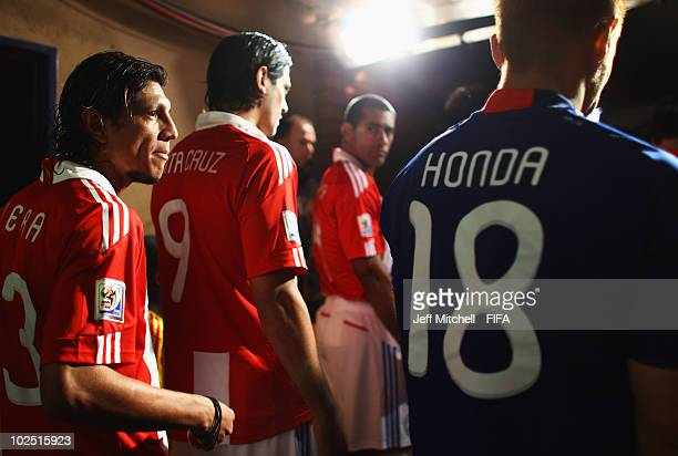 Claudio Morel of Paraguay looks across at Keisuke Honda of Japan in the tunnel ahead of the 2010 FIFA World Cup South Africa Round of Sixteen match...