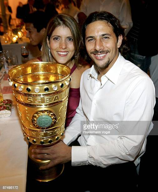 Claudio Pizarro and his wife Karla Salcedo pose with the trophy during the Bayern Munich party after the German Cup final between Bayern Munich and...
