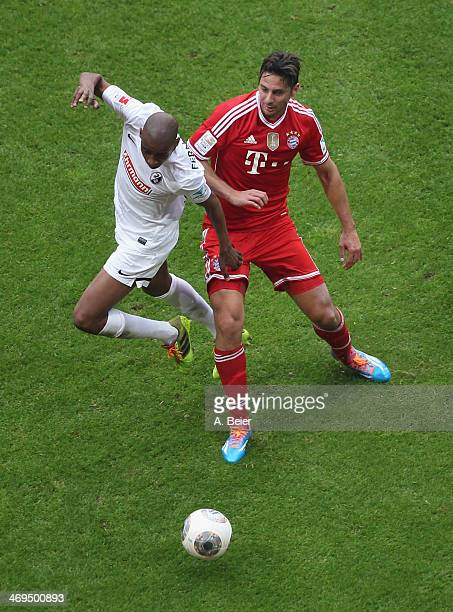 Claudio Pizarro of Bayern Muenchen fights for the ball with Gelson Fernandes of Freiburg during the Bundesliga match between FC Bayern Muenchen and...