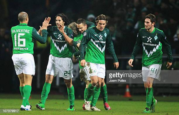 Claudio Pizarro of Bremen celebrates with his team mates after scoring his team's third goal during the UEFA Champions League group A match between...