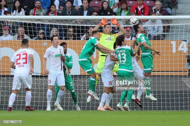 Claudio Pizarro of Bremen challenges Marco Richter of Augsburg during the Bundesliga match between FC Augsburg and SV Werder Bremen at WWKArena on...