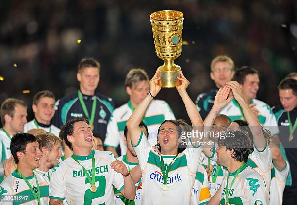 Claudio Pizarro of Bremen holds the trophy as the team celebrates their victory after the DFB Cup Final match between Bayer Leverkusen and Werder...