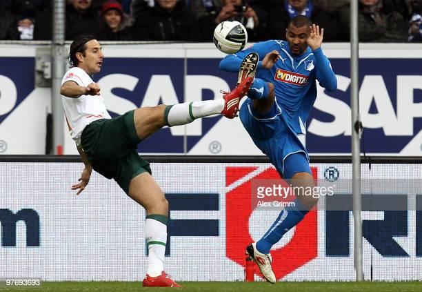 Claudio Pizarro of Bremen is challenged by Marvin Compper of Hoffenheim during the Bundesliga match between 1899 Hoffenheim and Werder Bremen at the...