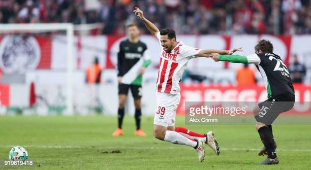 Claudio Pizarro of Koeln is held by Oliver Sorg of Hannover during the Bundesliga match between 1 FC Koeln and Hannover 96 at RheinEnergieStadion on...