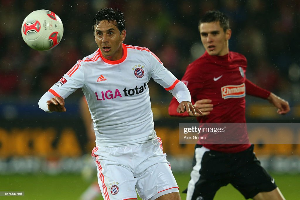 Claudio Pizarro (L) of Muenchen is challenged by Johannes Flum of Freiburg during the Bundesliga match between SC Freiburg and FC Bayern Muenchen at MAGE SOLAR Stadium on November 28, 2012 in Freiburg im Breisgau, Germany.